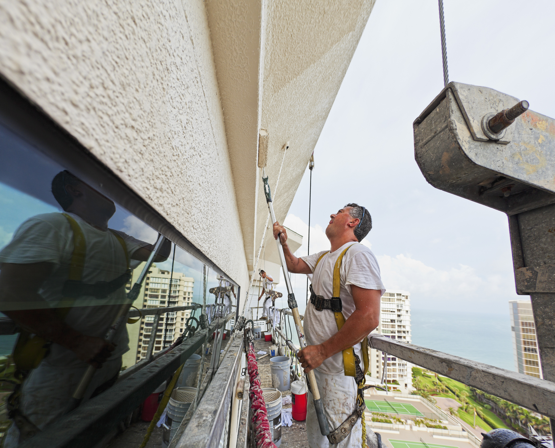 Two painters are painting a high rise building from a swing stage.